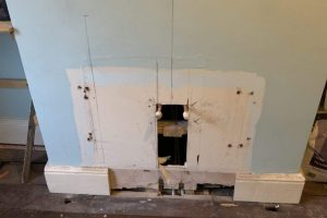 Radiator removed, pipes capped and old fireplace exposed